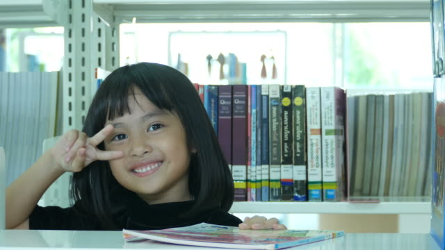 Victory Sign by Asian girl in library