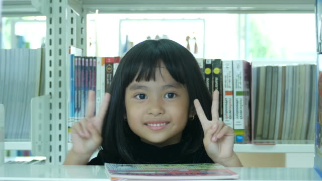Signo de la victoria por chica en biblioteca - vídeo