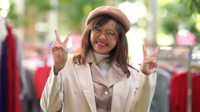 victory sign by mature businesswoman