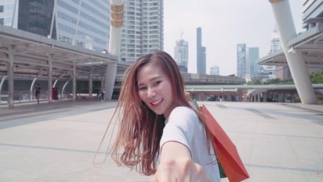 Video 4k: jonge vrouw haar vriend door de stad trekken, Happy vriendin maakt haar Man te volgen haar naar het winkelcentrum. video
