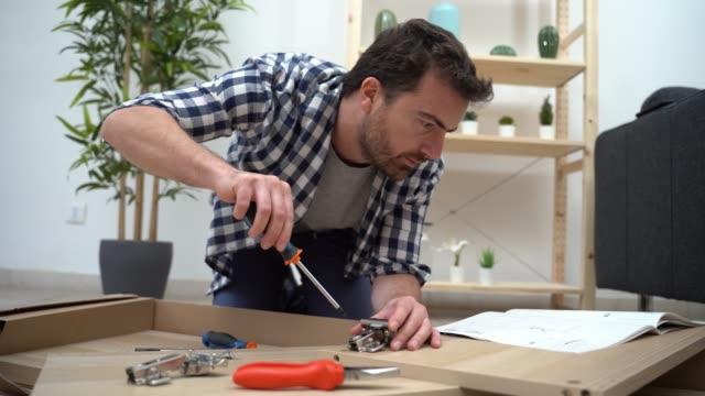 vídeos de stock e filmes b-roll de video about man portrait and do it yourself furniture assembly - bricolage