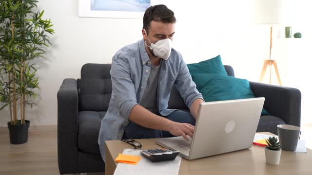 video about man teleworking from home after coronavirus pandemic - businessman covid mask video stock e b–roll