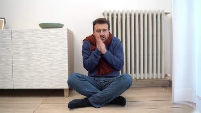 sıcak giysiler ile evde çok soğuk hissi bir adam hakkında video - dondurulmuş stok videoları ve detay görüntü çekimi