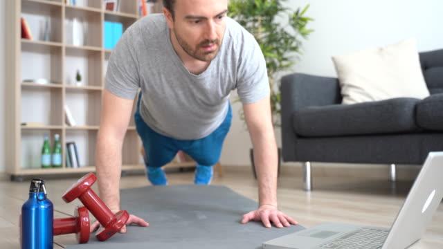 video om träning av en man hemma tittar på video tutorial - hemmaträning bildbanksvideor och videomaterial från bakom kulisserna