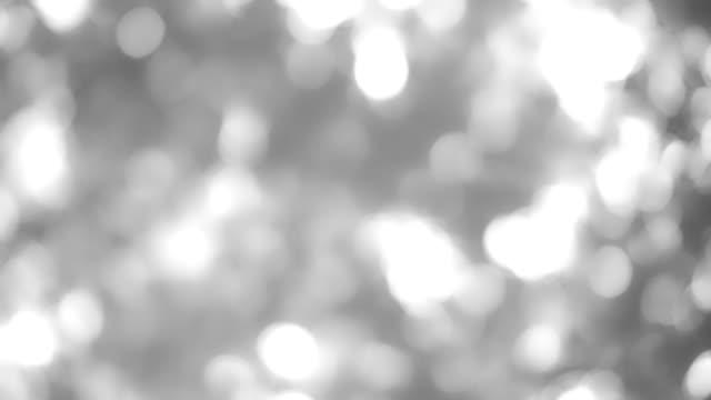 4kビデオ抽象孤立したぼかしお祝いのライトの葉植物は、ボケと美しい自然のボケと太陽光で風に揺れる影を残し、抽象的なぼやけた背景。 - 木漏れ日点の映像素材/bロール