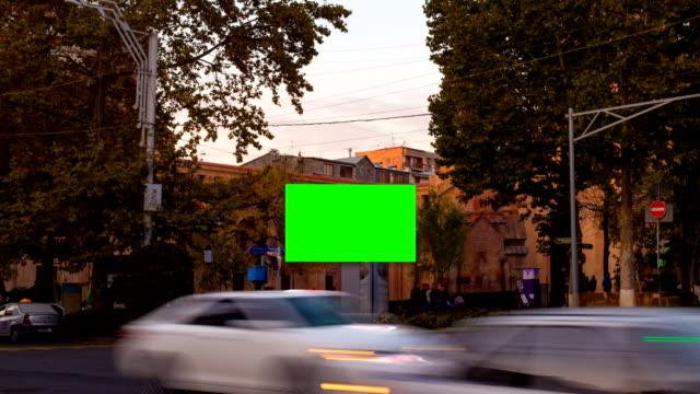 time lapse video. werbe-billboard mit grüner leinwand in der mitte des herbstlichen stadtbildes mit verschwommenen gehern und autos. kamera nähert sich - poster stock-videos und b-roll-filmmaterial