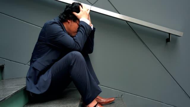 4 k ビデオ: アジアの無職の男を強調しました。大人の不安ありますうつ病や問題にドラッグを生活感悲しみ、孤独、心配に。 - 悩む点の映像素材/bロール