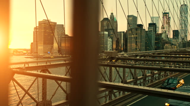 Video at sunset in Brooklyn Bridge against illuminated skyline