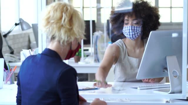 4k video business menschen durch ein acrylglas für soziale abstand getrennt, tragen schützende gesichtsmaske und diskutieren berater konzept, während covid-19 - hypothek stock-videos und b-roll-filmmaterial
