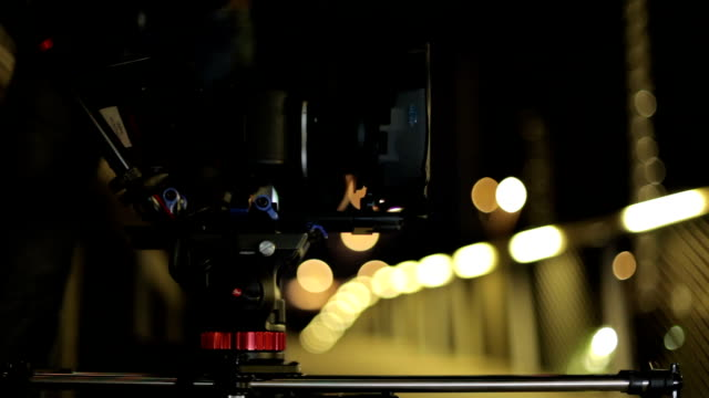 video camera on slider with beatiful lights in background. video