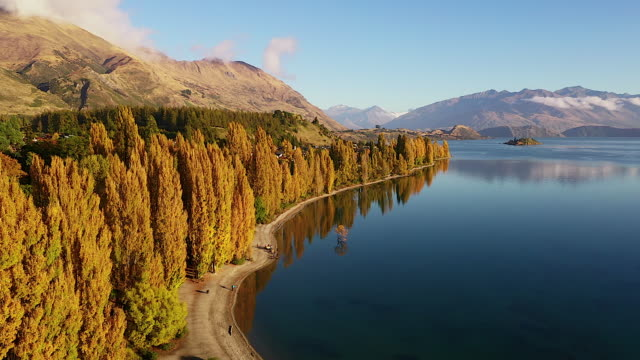 Video clip Drone flying over a beautiful lake By flying below to top There is a reflection of the face And in front of the snow-capped mountains is a concept of relaxation Natural travel