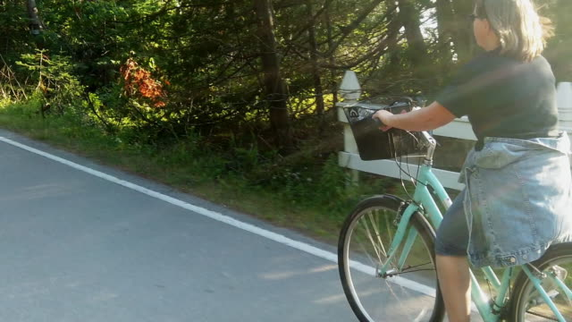 A Video Clip Of A Mature Smiling Woman Riding A Bicycle Enjoying The Scenery