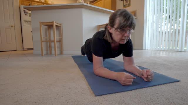 en video klipp av en aktiv senior woman på en yoga matta, utövar i sitt hem - mature women studio grey hair bildbanksvideor och videomaterial från bakom kulisserna