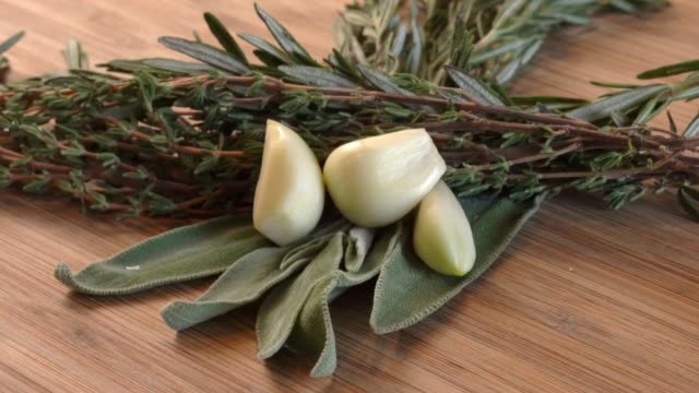 A Video Clip Of Aromatic Herbs, Garlic Cloves, Rosemary, Sage And Thyme Displayed On A Wood Cutting Board