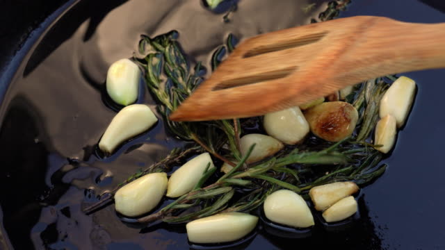 a video clip of rosemary and garlic cloves sauteed in a cast iron skillet with hot olive oil - przysmażany filmów i materiałów b-roll