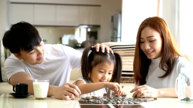 4 K Video: familia ahorrar dinero poniendo monedas en Banco cristal - vídeo