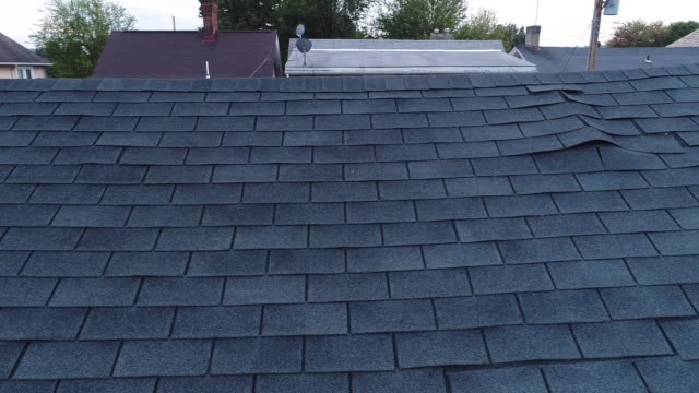 vídeos de stock e filmes b-roll de video feed of roof inspector and damaged shingles on roof - examinar