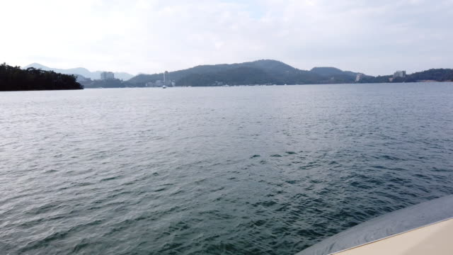 4k video footage pov forward tracking shot from the prow of a passenger ferry as it travels across waving water with mountaind and building background to sun moon lake, taiwan. - passenger craft stock videos & royalty-free footage