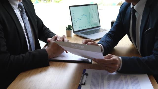 vidéos et rushes de 4k séquences vidéo de deux gens d'affaires comité de discussion au cours d'un entretien d'embauche la lecture d'un chercheur de curriculum vitae pour le recrutement parler dans le bureau - book