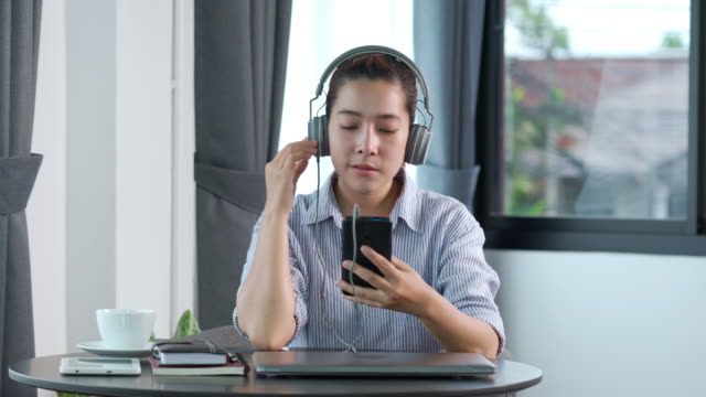 4K video footage of Young asian woman using smartphone listening to music on through headphones