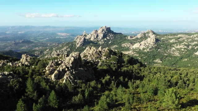 video from above, aerial view of a beautiful valley surrounded by granite mountains and green vegetation, monte limbara, sardinia, italy. - sardegna video stock e b–roll