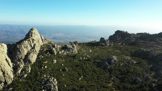 vidéos et rushes de vidéo par dessus, une vue aérienne d'une belle vallée entourée de montagnes de granit et de végétation verdoyante, monte limbara, sardaigne, italie. - randonnée équestre