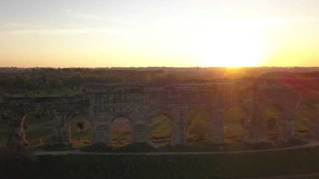 Video from above. Aerial view of the ancient ruins of the Roman aqueduct at sunset surrounded by a green park where people go running or spending the weekend. Parco degli Acquedotti, Rome, Italy. video
