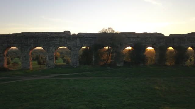 video from above. aerial view of the ancient ruins of the roman aqueduct at sunset surrounded by a green park where people go running or spending the weekend. parco degli acquedotti, rome, italy. - stile classico romano video stock e b–roll