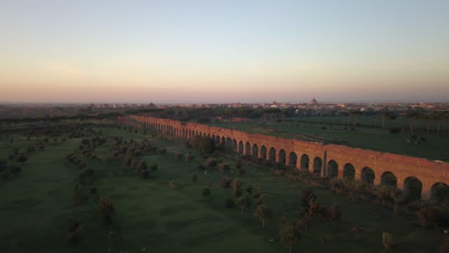 Video from above. Aerial view of the ancient ruins of the Roman aqueduct at sunset surrounded by a green park where people go running or spending the weekend. Parco degli Acquedotti, Rome, Italy. Video from above. Aerial view of the ancient ruins of the Roman aqueduct at sunset surrounded by a green park where people go running or spending the weekend. Parco degli Acquedotti, Rome, Italy. aqueduct stock videos & royalty-free footage