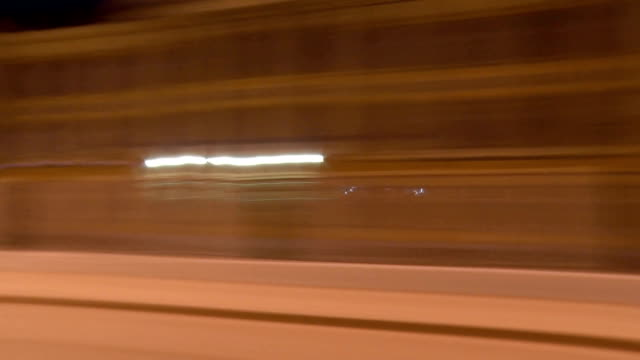 Video from the car window, driving through the night or the evening city. Time-lapse recording. A blurred abstraction video