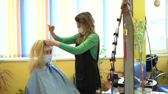 stockvideo's en b-roll-footage met 4k video kapper bleken strengen van blonde vrouw haar met een rubberen hoed in schoonheidssalon, tijdens covid-19 - mirror mask
