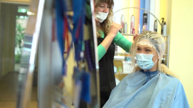 4kビデオ美容師は、美容院でゴム製の帽子でブロンドの女性の髪のストランドを漂白, covid-19中 - 美容室のビデオ点の映像素材/bロール