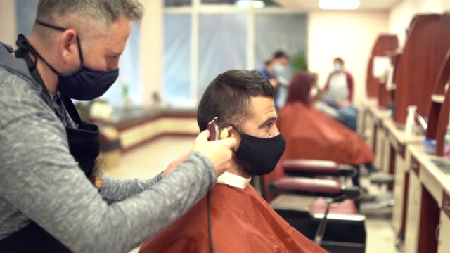 4K Video Hairdressers cutting hair with electric razor, during COVID-19 4K Video Hairdressers cutting hair with electric razor, during COVID-19 face mask videos stock videos & royalty-free footage