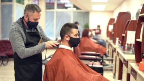 vidéos et rushes de 4k vidéo coiffeurs couper les cheveux avec un rasoir électrique, au cours de covid-19 - coiffure