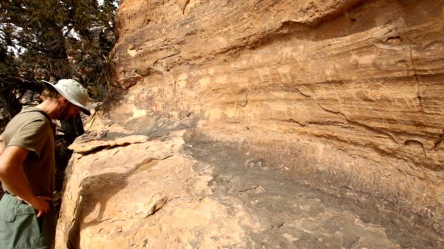 HD video Hiker inspects petroglyphs Southeast Colorado video