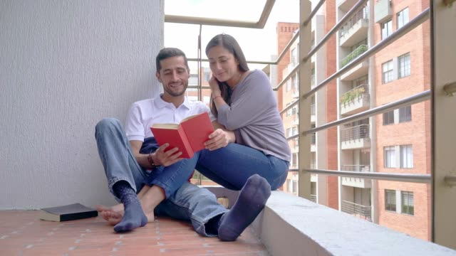 video in zeitlupe: verliebtes paar liest ein buch - lateinische schrift stock-videos und b-roll-filmmaterial