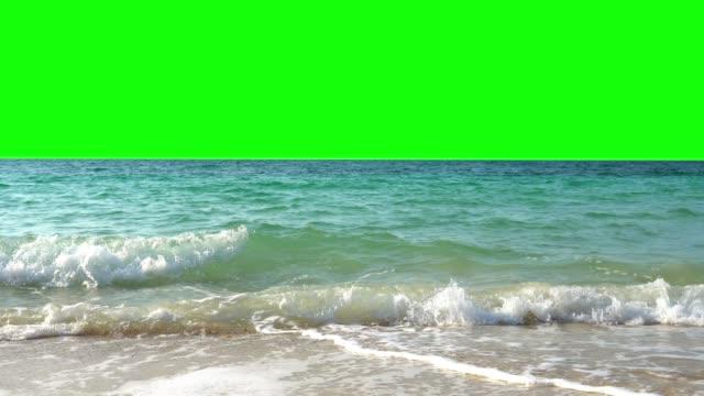 4k video paesaggio ampio scatto di onde d'acqua di mare blu che sguazzano sulla spiaggia di sabbia tropicale dell'isola con sfondo verde chiave chroma. i bagliori scintillanti del sole che sbirciano sulla superficie del mare. - gommapiuma video stock e b–roll