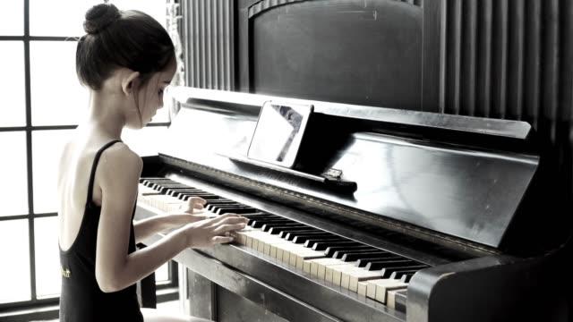vidéos et rushes de 4k vidéo monochrome focus sélectif moyen tourné vue arrière de la jeune belle petite fille en justaucorps noir assis et jouant du piano avec tablette en studio. - une seule petite fille