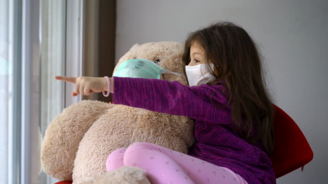 4K Video of a cute little girl whit protective mask standing next to the window with her teddy bear 4K Video of a cute little girl whit protective mask standing next to the window with her teddy bear face mask videos stock videos & royalty-free footage