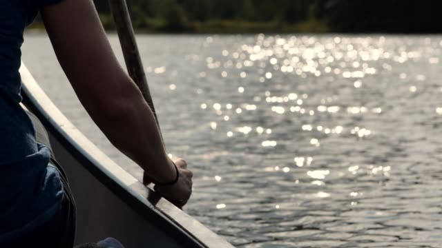 Video of a Portuguese woman canoeing on a lake at sunset.