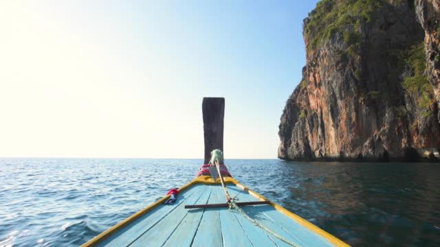 伝統的なロングテールボートのビデオは、いくつかの美しい石灰岩の山の周りを航行します。ピピ島、マヤ湾、クラビ県、タイ。 - サムイ島点の映像素材/bロール