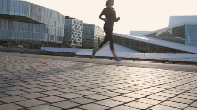 vidéos et rushes de vidéo d'une femme faisant de l'exercice tôt le matin. - joggeuse