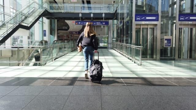 stockvideo's en b-roll-footage met video van een vrouw die loopt in een luchthaven. - vliegveld vertrekhal
