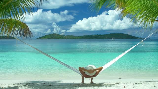 video van een vrouw swingen in hangmat op het strand video