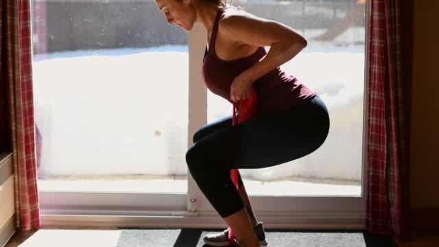 video von einer frau, die zu hause trainiert. - fitnessausrüstung stock-videos und b-roll-filmmaterial