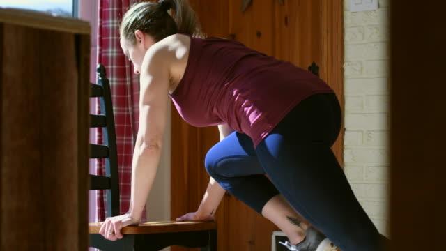vídeos de stock e filmes b-roll de video of a woman training at home. - chair