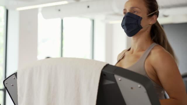 vídeos de stock e filmes b-roll de video of a woman training in a gym. - aparelho de musculação