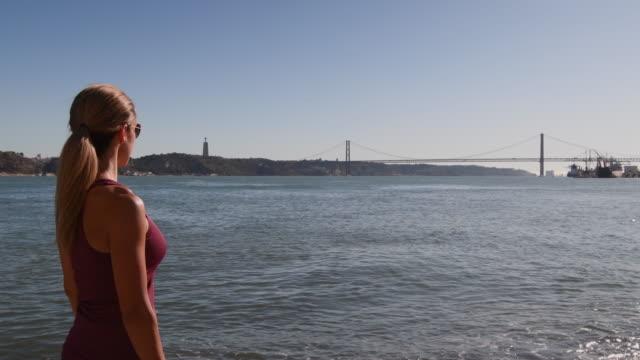 vídeos de stock e filmes b-roll de video of a woman visiting lisbon. - ponte 25 de abril