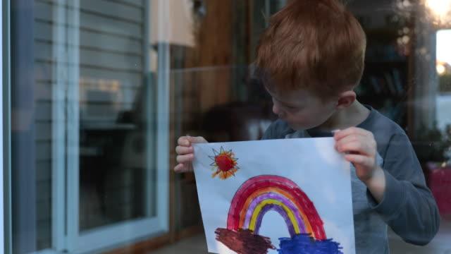 stockvideo's en b-roll-footage met 4k video van een jonge jongen die zijn tekening op huisvenster tijdens de crisis covid-19 plakt - buren