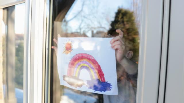 4k video von einem jungen jungen, der seine zeichnung während der covid-19-krise auf das fenster des heimfensters klebt - aufkleber stock-videos und b-roll-filmmaterial